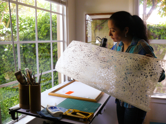 Photo of Nara holding decorative paper in preparation for framing a new painting.